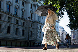 © Licensed to London News Pictures. 16/06/2021. London, UK. A woman uses an umbrella to shelter from the sun during hot weather near St James's Park in Central London. Temperatures are expected to rise with highs of 30 degrees forecasted for parts of London and South East England today . Photo credit: George Cracknell Wright/LNP