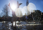 A man does a handstand as he participates in the 14th annual Polar Bear Plunge at Matthews Beach Park in Seattle on New Year's Day, 2016.  (Lindsey Wasson / The Seattle Times)
