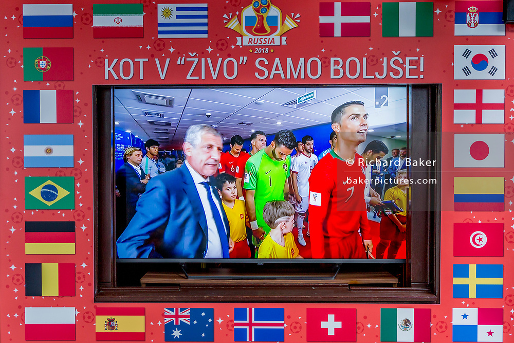 """The Portuguese and Spanish football teams are shown on a street TV screen bordered by international flags before their game in the 2018 World Cup in Russia, in the Slovenian capital, Ljubljana, on 25th June 2018, in Ljubljana, Slovenia. Above the screen it reads: """"Just like in the living room just better."""""""