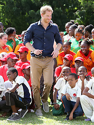 Prince Harry plays cricket during a community sports event at Queens Park Grounds in Grenada, during the second leg of his Caribbean tour.