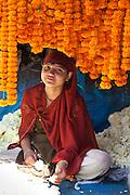 Young Indian girl stringing marigolds in ceremonial Brahmin garlands at Mehrauli Flower Market, New Delhi, India