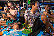 22 NOVEMBER 2013 - BANGKOK, THAILAND:  Performers with the Prathom Bunteung Silp mor lam troupe put on their makeup before a show in Bangkok. Mor Lam is a traditional Lao form of song in Laos and Isan (northeast Thailand). It is sometimes compared to American country music, song usually revolve around unrequited love, mor lam and the complexities of rural life. Mor Lam shows are an important part of festivals and fairs in rural Thailand. Mor lam has become very popular in Isan migrant communities in Bangkok. Once performed by bands and singers, live performances are now spectacles, involving several singers, a dance troupe and comedians. The dancers (or hang khreuang) in particular often wear fancy costumes, and singers go through several costume changes in the course of a performance. Prathom Bunteung Silp is one of the best known Mor Lam troupes in Thailand with more than 250 performers and a total crew of almost 300 people. The troupe has been performing for more 55 years. It forms every August and performs through June then breaks for the rainy season.     PHOTO BY JACK KURTZ