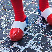 A man wearing colorful wooden shoes on a confetti covered stone street during a carnival (Fastnacht) parade in Basel, Switzerland.