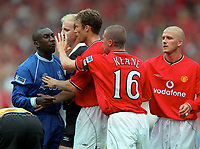 Roy Keane (Man Utd) reacts angrily to a tackled by Jimmy Floyd Hasselbaink (Chelsea). Referee Mike Riley, Ronny Johnsen and David Beckham (Man Utd) try to calm the situation down. Chelsea v Manchester United. FA Charity Shield. Wembley 13/8/00. Credit: Colorsport.