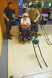 Staff and volunteer with visually-impaired wheel chair user at ten pin bowling alley.