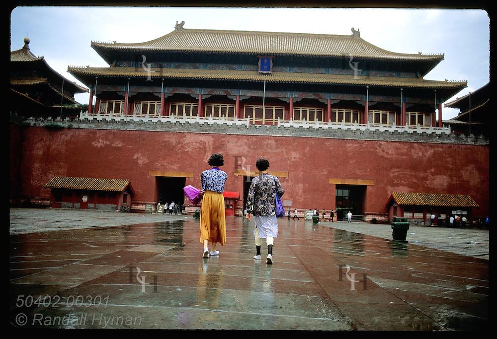 Two women walk toward the Forbidden City's entrance across vast exterior courtyard; Beijing. China
