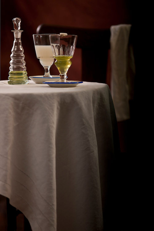Tablecloth, sur la table. Formal table setting serving two glasses of absinthe, one louched (opaque) and one, unlouched clear (green liquid) served in absinthe glasses on bistro dishes. A topette with absinthe also sits table. Reflections of the  Belle Époque.