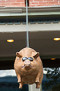 A pig sculpture hanging outside the Blind Pig restaurant in the Old Town historic shopping and restaurant district in Fort Collins, Colorado.