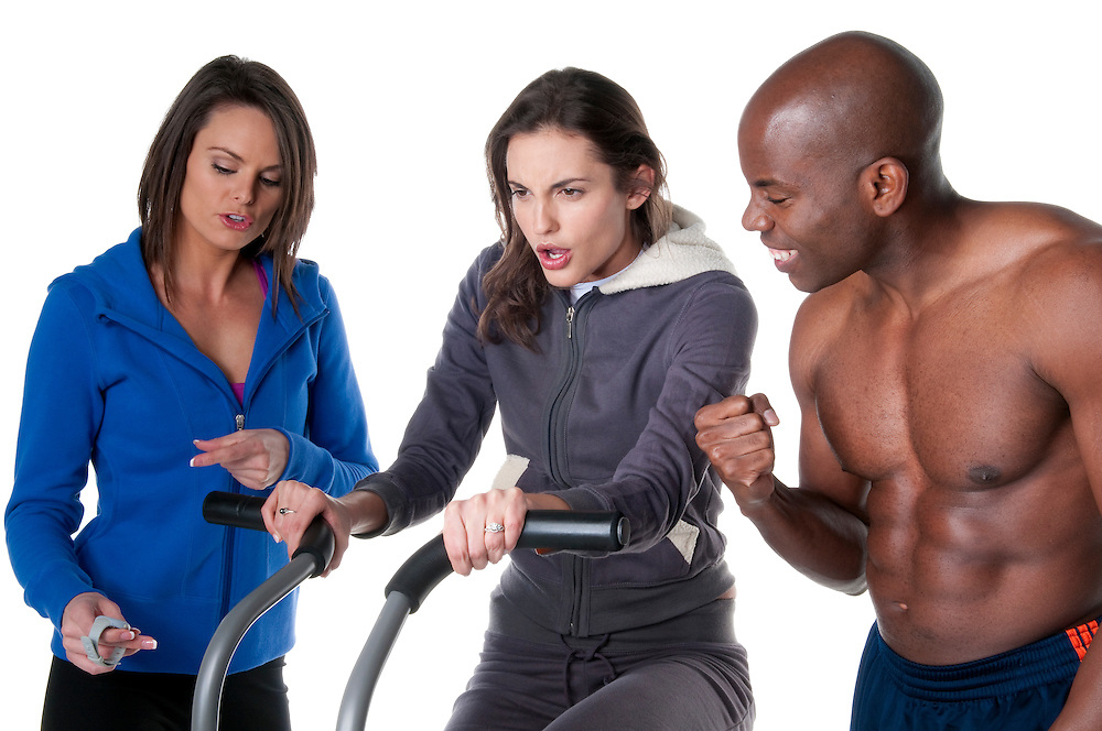 Young caucasian woman trainning in the gym with personal trainer and friend.