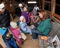 Christa Chapman watches along with her children Finn and Sadie as Maya chooses a face painting design by Laura Blouin during Prescott Farm's 2nd annual Winter Fest Saturday afternoon.  (Karen Bobotas/for the Laconia Daily Sun)