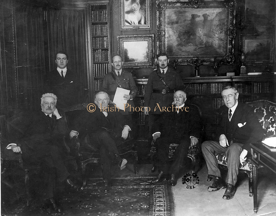Council of Four at the Versailles Peace Conference 1918.  Left to right: Vittorio Emmanuele  Orlando, Prime Minister of Italy;  David Lloyd George, Prime Minister of Britain; Georges Clemenceau, Prime Minister of France,  and (Thomas) Woodrow Wilson, President of the USA. Standing are confidential secretaries.