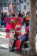 San Francisco, USA. 19th January, 2019. The Women's March San Francisco begins with a rally at Civic Center Plaza in front of City Hall. A woman sits by her hats for sale, including pussy hats, and knits a pink pussy hat as the crowd gathers before the rally. Credit: Shelly Rivoli/Alamy Live News