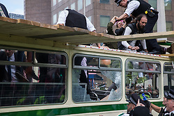 Metropolitan Police officers climb onto a vintage bus used by Extinction Rebellion activists to block a road junction to the south of London Bridge on the ninth day of their Impossible Rebellion protests on 31st August 2021 in London, United Kingdom. Extinction Rebellion are calling on the UK government to cease all new fossil fuel investment with immediate effect.
