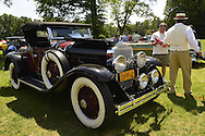 Old Westbury, New York, U.S. - June 1, 2014 -  A red and black 1927 La Salle 303 Roadster, owner JOHN MICCICHE of SMITHTOWN holding fire extinguisher, is an entry at the Antique and Collectible Auto Show held on the historic grounds of elegant Old Westbury Gardens in Long Island, and sponsored by Greater New York Region AACA Antique Automobile Club of America.