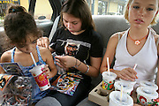 (MODEL RELEASED IMAGE). On the way back from Mackas (Aussie slang for McDonald's), 15-year-old Kayla Samuals (in 50 Cent T-shirt) rips open the Spy Kids 3-D comic book that the restaurant awards to purchasers of Happy Meals. Like her half-sister Sinead Smith (drinking) and her friend Amelia Wilson, Kayla is from an Aboriginal family whose roots lie in the arid outback. But the girls have little interest in outback cuisine; at least for now, Mackas is their culinary mecca. Hungry Planet: What the World Eats (p. 13).  The Brown family is one of the thirty families featured, with a weeks' worth of food, in the book Hungry Planet: What the World Eats.