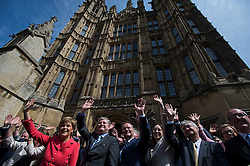 © London News Pictures. 11/05/2015. Leader of the SNP Nicola Sturgeon (left in red top) is applauded by 56 SNP Members of Parliament outside the St Stephens Entrance to the Houses of Parliament  as they arrive at Westminster following their election sucess. Photo credit: Ben Cawthra/LNP