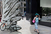 A lady holds on to her wide-brimmed hat while walking past the sculpture entitled City Wing on Threadneedle Street in the City of London, the capital's financial district (aka the Square Mile), on 11th July 2019, in London, England. City Wing is by the artist Christopher Le Brun. The ten-metre-tall bronze sculpture is by President of the Royal Academy of Arts, Christopher Le Brun, commissioned by Hammerson in 2009. It is called 'The City Wing' and has been cast by Morris Singer Art Founders, reputedly the oldest fine art foundry in the world.