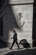 Passers-by beneath a carved anchor in the Square Mile, the capitals financial district, on 31st March 2017, in the City of London, England.