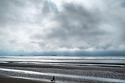 Lone figure walking dog along sandy beach enjoying the solitude by the Bristol Channel at Burnham-on-Sea, Somerset, UK