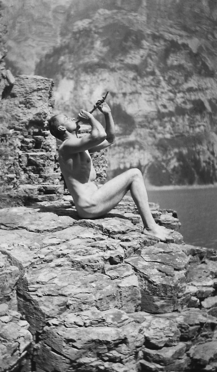 Nude man sitting on the rocks and playing musical instrument, 1922