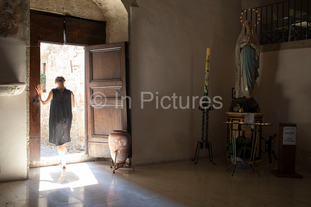 Woman passing the Virgin Mary figurine looking over in the Church of San Silvestro in Bevagna, Umbria, Italy.
