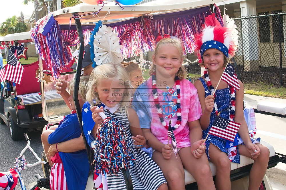 Young girls smile as they ride along in a golf cart decorated in patriotic bunting during the annual Sullivan's Island Independence Day parade July 4, 2017 in Sullivan's Island, South Carolina. The tiny affluent sea island hosts a bicycle and golf cart parade through the historic village.