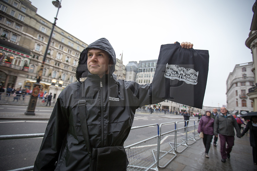 © Licensed to London News Pictures . 17/04/2013 . London , UK . A newspaper seller holds a limited edition Daily Telegraph in a black bag outside Charring Cross Station . The funeral of former British Conservative Prime Minister , Baroness Margaret Thatcher , today (Wednesday 17th April 2013) in Central London . Baroness Thatcher died from a stroke at the age of 87 . Photo credit : Joel Goodman/LNP