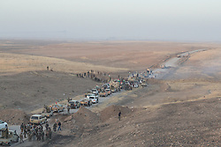 20/10/2016. Bashiqa, Iraq. Pickup trucks and armoured vehicles belonging to Iraqi-Kurdish peshmerga fighters queue as they begin to drive into no-mans land as part of an operation to retake Mosul from Islamic State militants today (20/10/2016). <br />