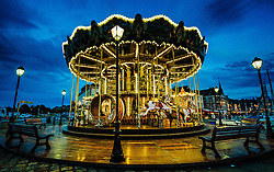 The famous old carousel which offers rides beside the harbour in Honfleur, France