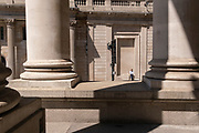 Seen through the columns of Royal Exchange, a man waits patiently for someone or something beneath the architecture of the Bank of England on Threadneedle Street in the City of London, the capital's financial district, on 8th June 2021, in London, England.