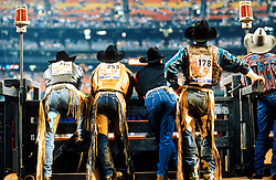 Cowboys watching the rodeo from a participant's gate