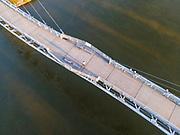 Aerial photograph of the Bob Kerrey Pedestrian Bridge that spans the Missouri River between Council Bluffs, Iowa and Omaha, Nebraska on a beautiful morning.