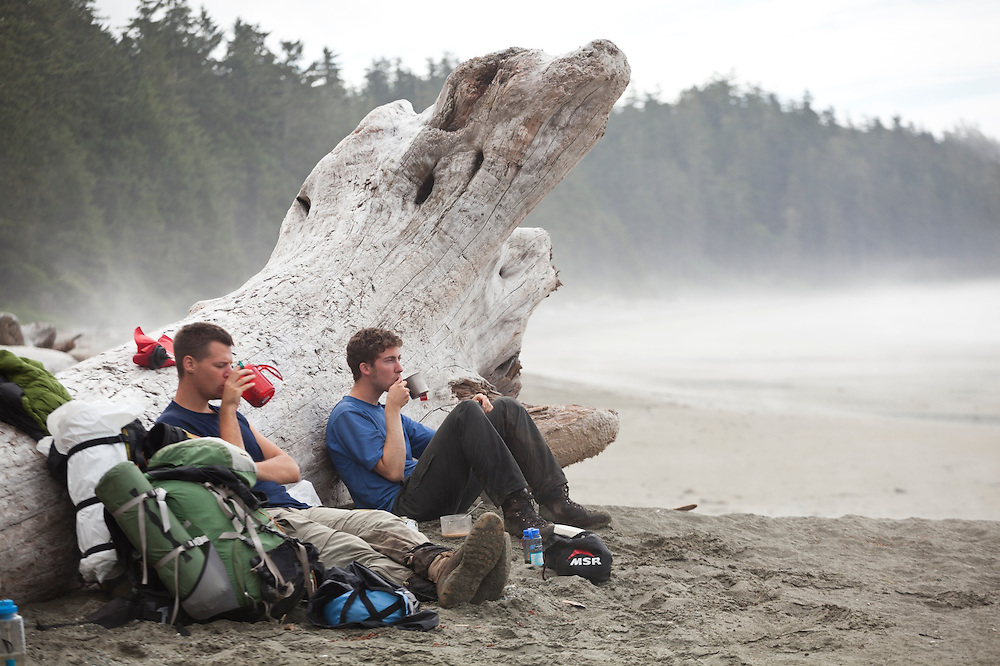 Henry (left) and Zach Podell-Eberhardt sit against a giant driftwood log sipping hot tea on a beach along the West Coast Trail, British Columbia, Canada.