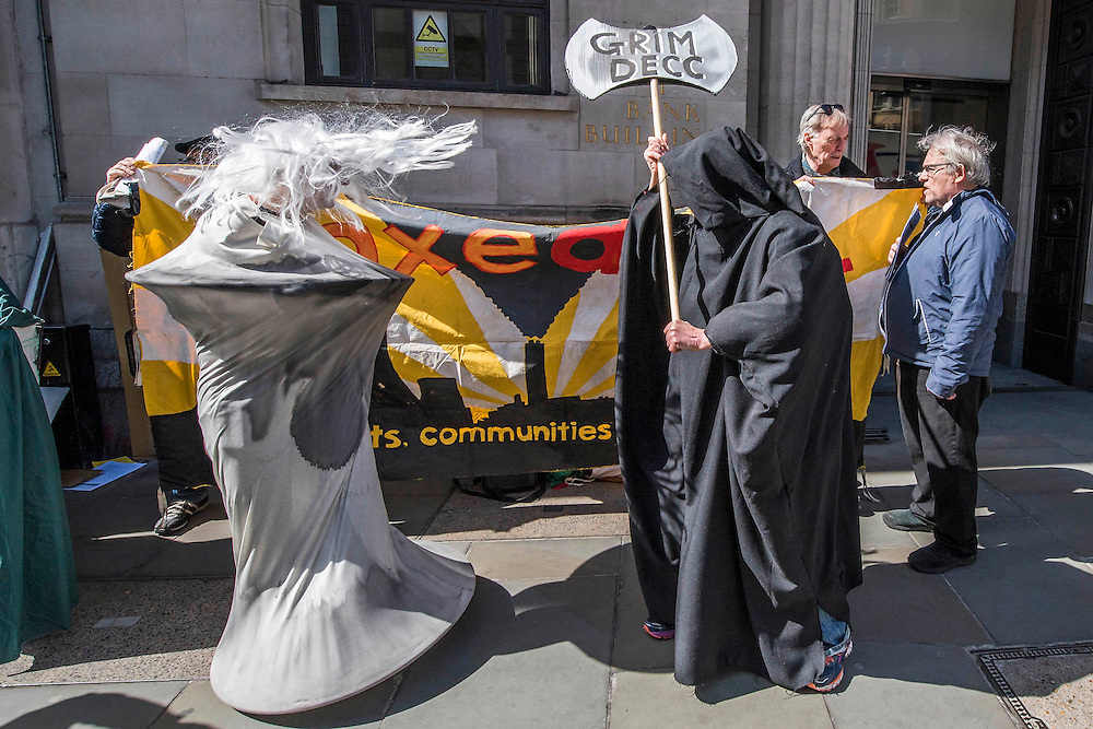 A woman dressed as a cooling tower is axed by the grim reaper - #AxeDrax protest outside the annual Drax shareholder AGM. Protestors demanded cleaner, greener energy generation systems. They continued on to the Department of Energy and Climate Change to deliver a petition demanding that subsidies given to Drax, for burning biomass, be stopped for making climate change worse.