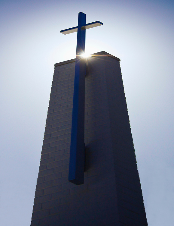 Aiming up photo of church steeple with sun behind the cross