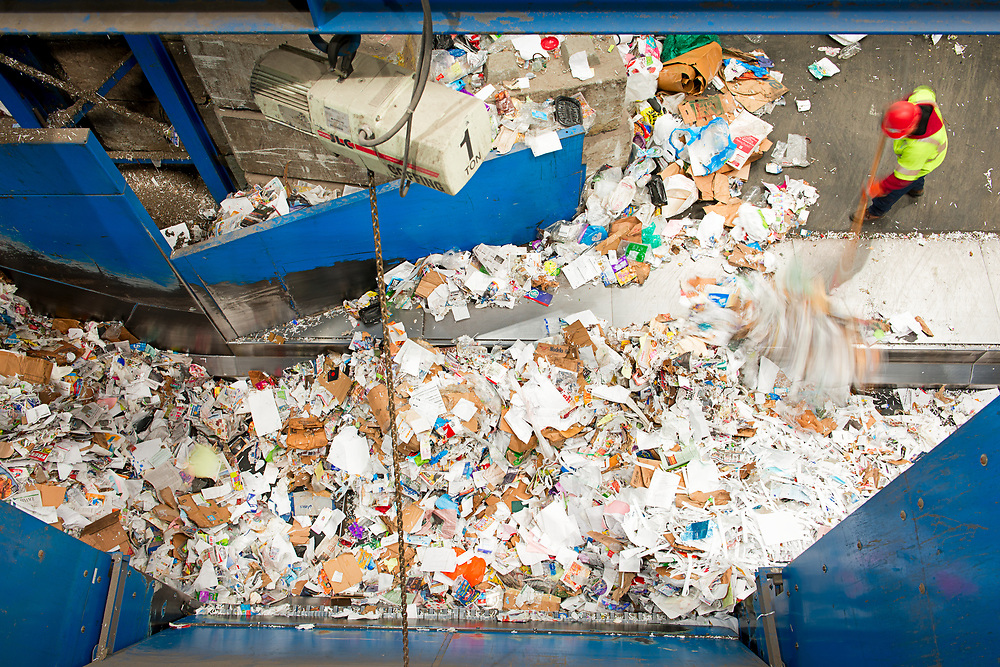 A worker sweeps paper back on to the conveyer belt moving the material from the mrf floor through the sorting process.