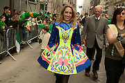 A young woman in Irish dance costume walks in the parade.