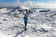 A teenage girl takes pictures at Cave Point County Park on Lake Michigan near Sturgeon Bay, Wisconsin on a cold winter day.