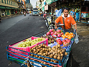 """11 AUGUST 2016 - BANGKOK, THAILAND:   A fruit seller pushes his cart past Pak Khlong Talat. Pak Khlong Talat (literally """"the market at the mouth of the canal"""") is the best known flower market in Thailand. It is the largest flower market in Bangkok. Most of the shop owners in the market sell wholesale to florist shops in Bangkok or to vendors who sell flower garlands, lotus buds and other floral supplies at the entrances to temples throughout Bangkok. There is also a fruit and produce market which specializes in fresh vegetables and fruit on the site. It is one of Bangkok's busiest markets and has become a popular tourist attraction.          PHOTO BY JACK KURTZ"""