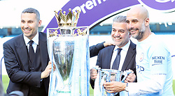 Manchester City chairman Khaldoon Al Mubarak (left) and manager Pep Guardiola (right) celebrate with the Premier League trophy and League Cup after the Premier League match at the Etihad Stadium, Manchester.