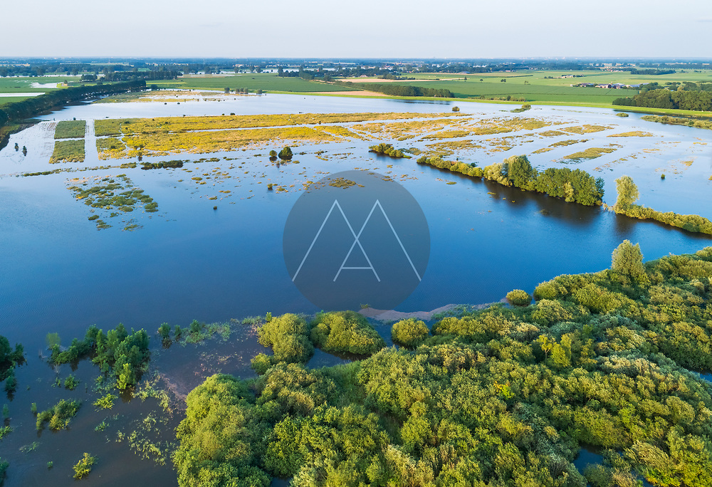 Aerial view of flooded floodplains of river Maas with submerged road during a period of high water in summer, Megen, Noord-Brabant, The Netherlands.