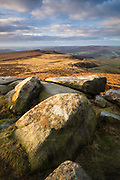 Higger Tor's shapely gritstone rocks make a bold foreground for this classic scene in the Peak District. Hathersage Moor, Over Owler Tor, Millstone Edge and the Derwent Valley can be seen in the distance. A winter landscape in England, UK.