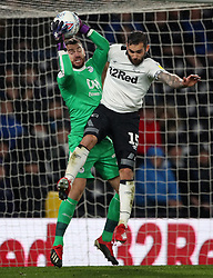 Derby County's Bradley Johnson and Wigan Athletic goalkeeper Jamie Jones battle for a high ball during the Sky Bet Championship match at Pride Park, Derby.