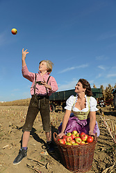 Mother and son playing with apples in field, Bavaria, Germany