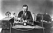 Guglielmo Marconi (1874-1937), Italian physicist and inventor. Radio pioneer. Marconi with typical apparatus, including 10-inch induction coil spark transmitter (right), morse inker and 'grasshopper' key in centre. Photograph.