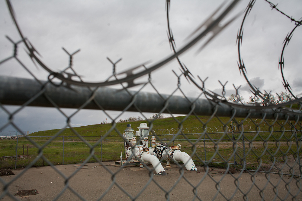 A pump next to a levee along the Feather River is surrounding by chain link and razor wire. No levee is perfect, and pumping of under-seepage is necessary during the rainy season. March 21, 2009.