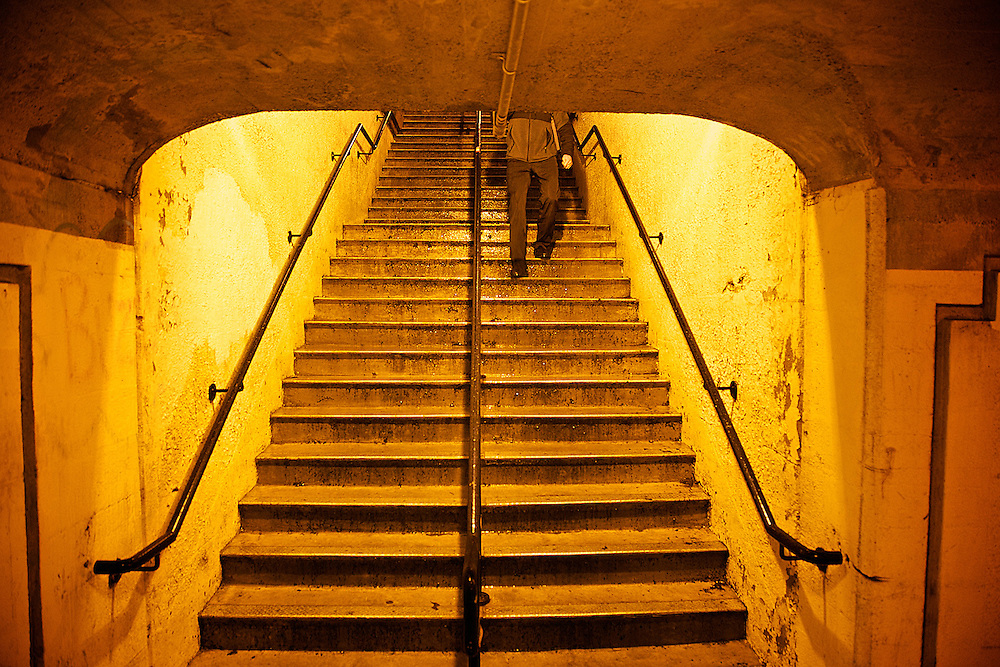 A commuter off a train from New York, descends the stairs at the West portal.