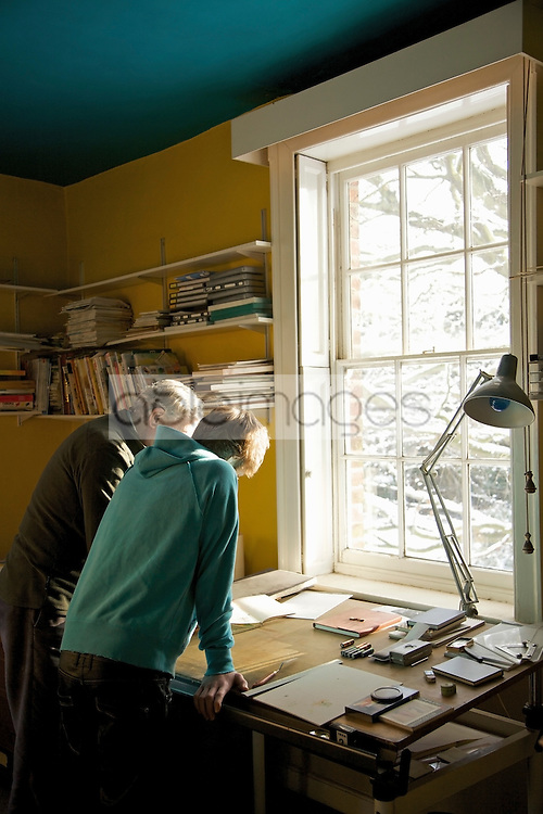 Back view of two men leaning over a desk