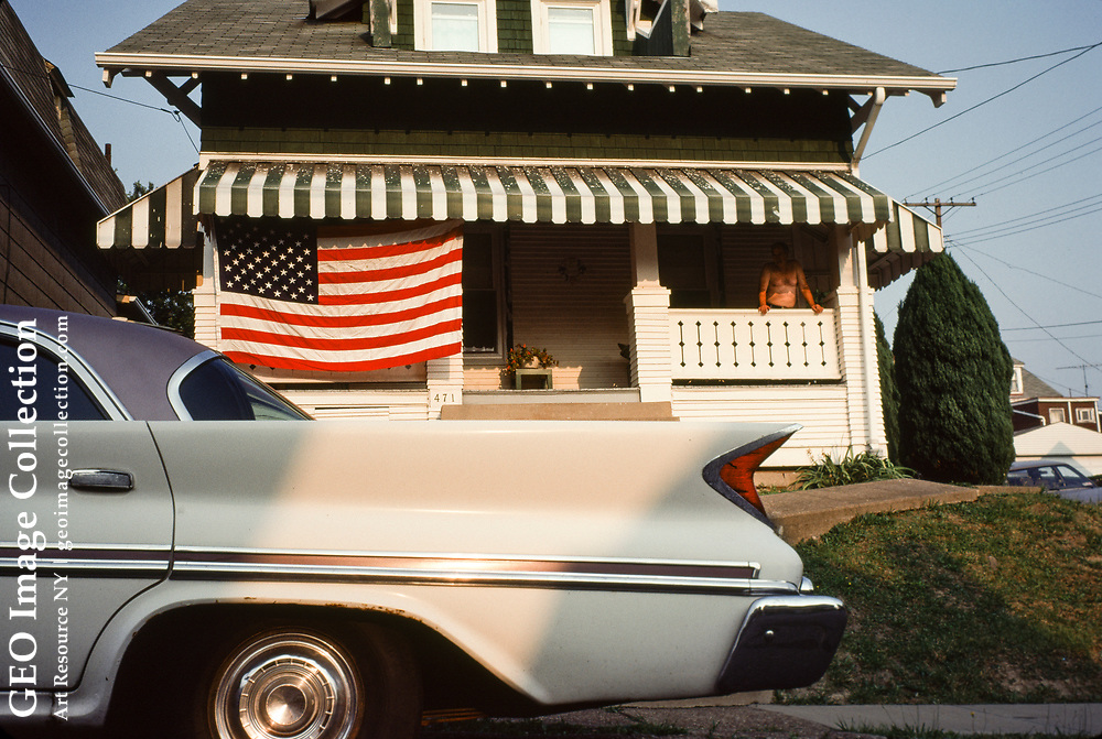 Modest bungalow house is decorated with American flag to express patriotism on the Fourth of July or Independence Day holiday. The circa 1960 car with tail fin in foreground is a Chrysler sedan automobile with tailfins introduced in the 1950's.  The house is on Edith Street in the residential Duquesne Heights neighborhood and home to many working class families.