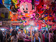 """27 NOVEMBER 2012 - BANGKOK, THAILAND:  A balloon vendor at the Wat Saket Temple Fair in Bangkok. Wat Saket, popularly known as the Golden Mount or """"Phu Khao Thong,"""" is one of the most popular and oldest Buddhist temples in Bangkok. It dates to the Ayutthaya period (roughly 1350-1767 AD) and was renovated extensively when the Siamese fled Ayutthaya and established their new capitol in Bangkok. The temple holds an annual fair in November, the week of the full moon. It's one of the most popular temple fairs in Bangkok. The fair draws people from across Bangkok and spills out in the streets around the temple.   PHOTO BY JACK KURTZ"""